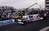 Tony Schumacher, left, and Morgan Lucas, right, take off from the start for the Top Fuel Finals on...