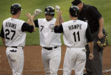 Colorado Rockies' catcher, #7, J.D. Closser, center, is congratulated by #27, Garrett Atkins,...