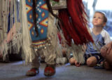 Damian Morales, cq, 4, Fort Collins, watches Cathy Gervais of the Wind River Native American...