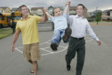 Three year old Joey gets a big swing from his daddy Dave Johnson (cq) (left) and his papa James...