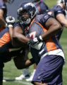 #67 Anthony Clement tries to spin away from George Foster #72 during a drill as the Denver ...