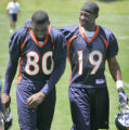 Broncos receivers #80 Rod Smith and #19 Jerry Rice kid around with each other as they walk off the...