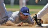 Colorado Rockies' center fielder,  #31, Cory Sullivan, races to first base beating the diving tag...