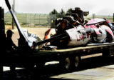 Kyle Cook of Beegles Aircraft Service loads the wreckage of a Tr-State CareFlight helicopter into...