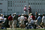 Being in the red is the desired color.  Golf fans stop to take a look at the leader board that...