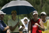 At the 8th hole, Michelle Wie (L) and competitor Brittany Lincicome (r)  share an umbrella as they...