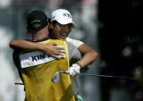 Birdie Kim, of Korea, hugs her caddie, Miles Nixon after sinking a chip shot from the sand trap...