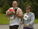 Ray Rocho (cq) carries his dog Milly while walking with his wife Cindy Rocho (cq), left to right,...