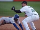 Omaha's Adrian Brown dive back to first base to beat the tag out by Sky Sox first baseman Ryan...