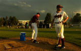 Foxes pitcher Nathan Jennings(cq), left, a sophomore from St. Edwards University, cleans the mound...