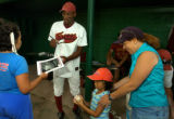 Foxes player Derrick Keeton (cq), in uniform, signs autographs for Shea Liggins(cq) 11, left, and...