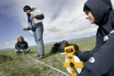 Louise Elinoff (cq, center) uses a GPS to establish a position while mapping out an effigy near...