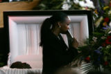 A mourner holding a program walks past the coffin of Javad Marshall Fields.  At the Mount Gilead...