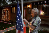 Floyd Bishop, Longmont, takes down the American flag as a rain storm moves in on Tuesday, June 28,...