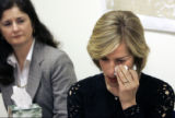 (CODER101) Charlotte Garrett (rt) wipes away tears at a press conference about her late husband...