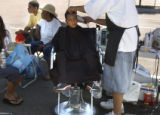 Deondre Garner-Jackson (cq),6, of Denver, Colo., holds still while getting his hair cut by Erik C....