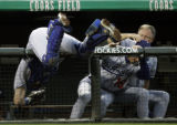Los Angeles Dodgers' catcher, #9, Jason Phillips, left, goes over the rail chasing a foul ball by...