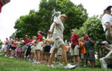 Flanked by security, Annika Sorenstam walks from the No. 4 green to tee off at No. 5 during her...