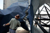 John Grant, Denver's public art administrator, steadies two leg pieces from Local sculptor...