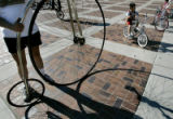 "Zane Cespedes, 5, right, of Denver, rides his little bicycle past a ""penny farthing""..."