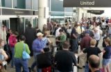 Air travelers wait outside of the west entrance to the main terminal of the Denver International...