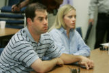 John Garrett(cq) left, and Jennifer Garrett-Buck, brother and sister of Jeff Garrett hold hands as...