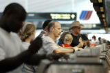 Denver, CO July 25, 2005 United Airlines customers obtain their boarding passes using the check in...