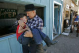 Jerry Risner (cq) carries his 5-year old son, John, in front of his roasted cinnamon almond stand...