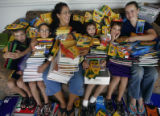 Brenda Finesilver, (cq) center left, with 5 of her 7 kids, under a pile of school supplies they've...