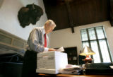 New CU President Hank Brown unpacks some items from a box in his office Monday on his first day on...
