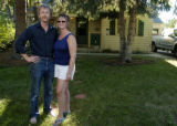 Bruce Wheelock(cq), left, and his wife Alyson Wheelock(cq), right, stand in front of their home in...