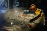 A confirmed passenger of Air France Flight 358 from Paris lies in the back of an ambulance with...