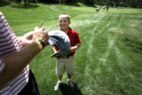 Jake Donahue, cq, 8, of Denver, enjoys getting his hat signed by Greg Owen on the 16th fairway...