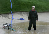 Groundskeeper Pierce Jacoway (cq) looks up to the sky while standing in a puddle of water in a...
