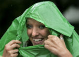 Courtney Inman (cq), 19, tries to stay dry in the rain by wearing a trash bag after play was...