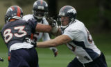 JPM190 - Denver Broncos John Engelberger, #60, sheds a block from tight end Mike Leach, #83,...