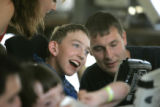 Mackenzie Port, 13, laughs with camp councilors as they talk using an augmentative and alternative...