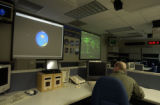 TSgt Jeffrey Fox  (cq) looks at projected images representing  the orbits of the International...