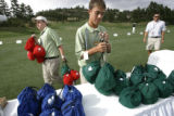 Range assistants Jeff Botkin, cq, 15, left, and Drew Schneider, cq, 14, center, replenish bags of...