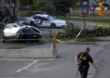 A Grand County, Colo., sheriff's deputy walks past damaged Granby, Colo.,  police cars that were...