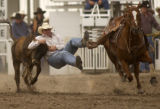 Cole Allen Fritzlan of Rifle, Colo., tries to bring down a steer during the Steer Wrestling event...