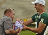 Chris Cessna (cq) takes his two week old daughter Aiden Cessna from CSU quarterback Justin...