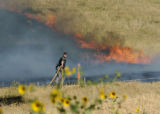 Golden, CO July 19, 2005 A Jefferson County sheriff's deputy assists Metro West firefighters as...
