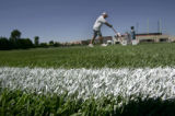 Denver Broncos Football Club's Brett Baird, cq, Assistant Turf Manager, repaints lines onto the...