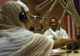 Kidane Teklu(cq), right, an Ethiopian immigrant, laughs during his radio show while Beza...