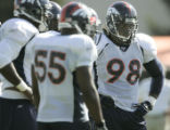 Denver Broncos' defensive end, Courtney Brown, right, waits in the defensive huddle during morning...