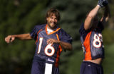 Denver Bronco quarterback, Jake Plummer, left, and tight end, Jeb Putzier, right, stretch before...