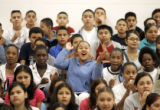 Students at Bruce Randolph Middle School cheer as teachers at the school are introduced for the...
