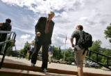 New CU President Hank Brown (left) walks past a student on the Boulder campus Monday on his way...