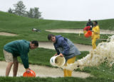 Groundskeepers Chad Rife, 19, bottom left, and Austin Nichols, 18, center bottom, use buckets to...
